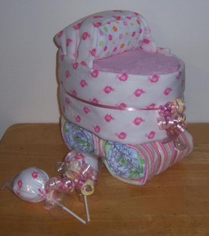 """1 Bassinet (Made with about 29 Diapers, 1 Gerber Receiving Blanket, 1 Gerber Cloth Diaper/Burp Cloth, 1 Pacifier, and about 5 Wash Cloths) *(measures about 10""""x9""""x7"""")  2 Lollipops (Made with matching Gerber bird gloves) *(measures about 3"""" wide x 5"""" tall)"""