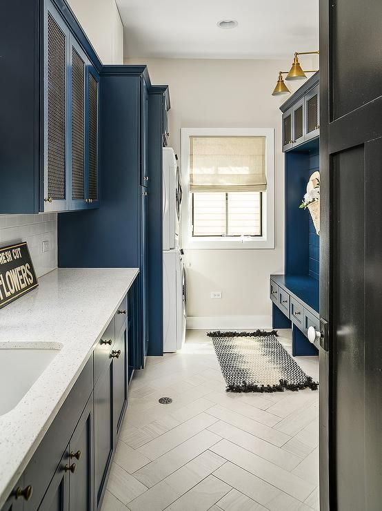 Transitional laundry and mudroom combined together featuring blue cabinets with metal lattice doors and nickel knobs. White quartz countertops and subway tiles lift the light hues in the laundry room along with light gray herringbone tiles. M House Development