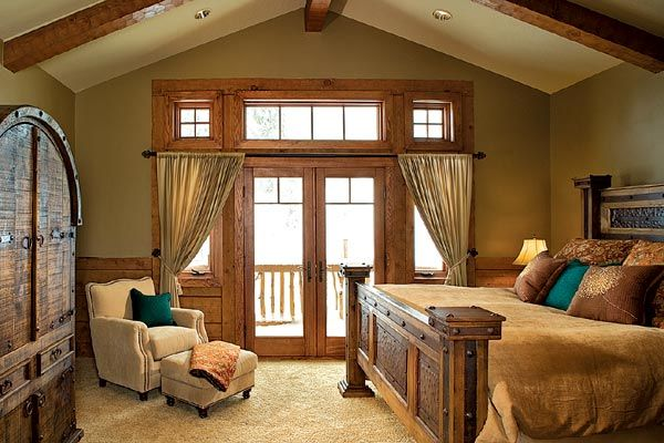 A vaulted ceiling lined with timber beams perfectly complements the elaborate four-post bed, reclaimed armoire and chalet-style windows in the master bedroom.