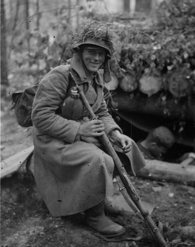 """A soldier at resting at dawn, sometime after fighting off enemy attempt to relieve it's troops surrounded in a """"motti"""". Ilomantsi area, 9 Aug 1944."""