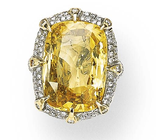 A YELLOW SAPPHIRE AND DIAMOND RING   Set with a cushion-cut sapphire weighing approximately 31.03 carats, enhanced by circular-cut diamond prongs, within a circular-cut diamond surround, with pavé-set diamond shoulders, mounted in white and yellow gold