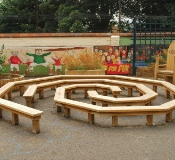 elevated wood bench seating on mulch; functions as maze