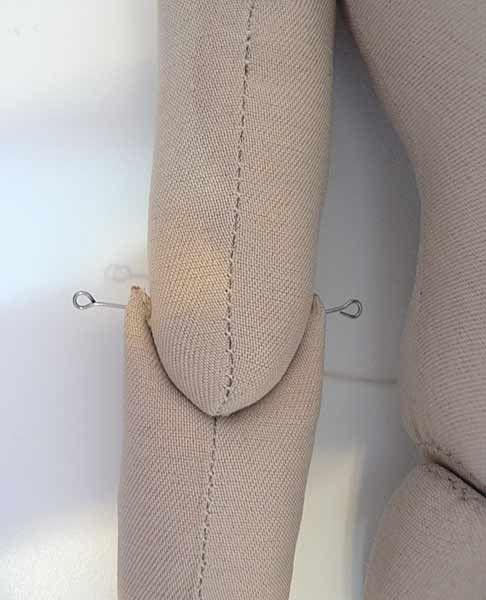 59 Пришиваем кисти к предплечью: выемку в кисти туго прижимаем к низу предплечья и фиксируем булавками. Прошиваем между булавок несколько раз.