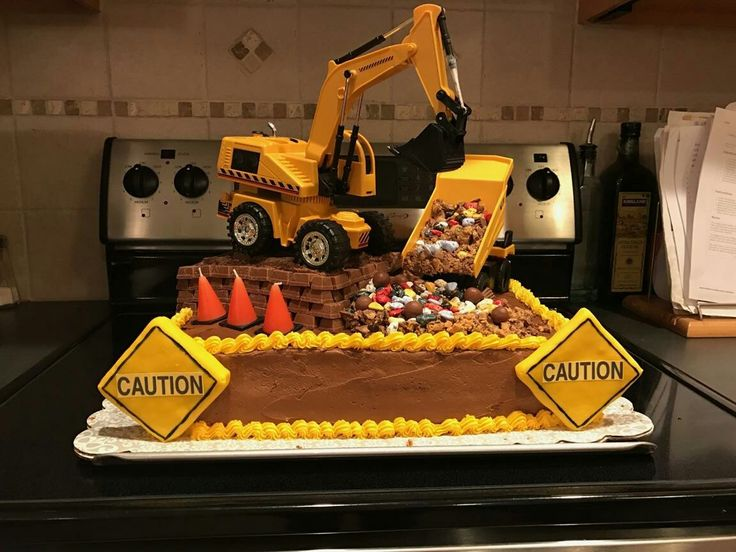 "Excavator Cake  Excavator is sitting on top of iced rice krispie square covered in chocolate graham cracker ""dirt"" & surrounded by kit kat ""bricks"".  Dump truck filled with chopped Reese PB ""dirt"" & edible chocolate rocks.  Orange cones are candles.  Caution signs are rice krispie squares wrapped in fondant, written in food writer ink.  This excavator actually digs the dirt/rocks.  R/C wire is buried thru the kit kats & behind piping on back of cake."