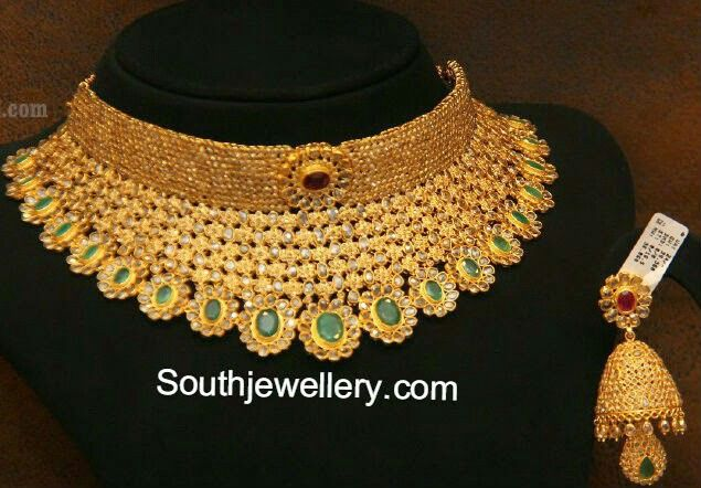 22 carat gold uncut diamond broad collar choker studded with uncut diamonds and emeralds teamed up with matching uncut diamond jhumkis from Malabar Gold and Diamonds.