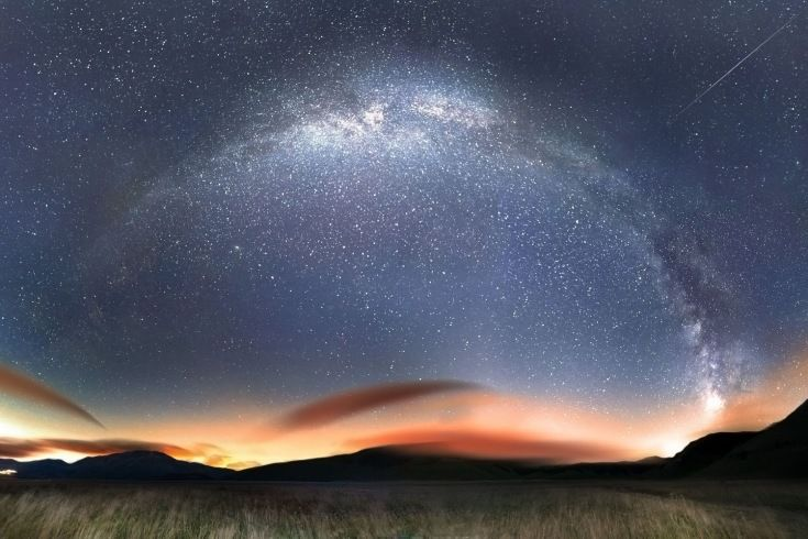 A rainbow is seen in space as a result of a star cluster millions of miles away, in Castelluccio Plateau, Sibillini Mountains National Park, Sibillini, Italy.
