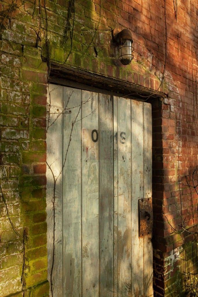 "Creaky Door - Photo of Hart Island. A fading sign reads ""DORMS."""