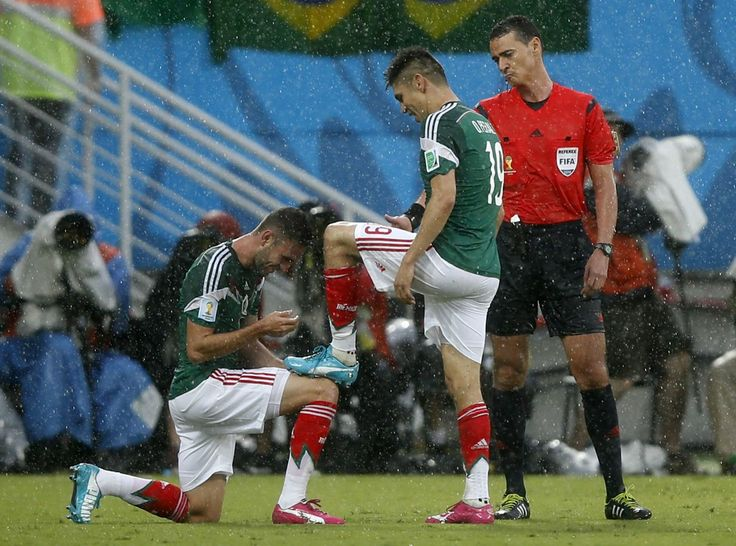 Mexico's Miguel Layun ties shoelaces for Mexico's Oribe Peralta after Peralta scored a goal during their 2014 World Cup Group A soccer match at the Dunas arena in Natal June 13, 2014.