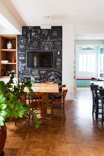 A mesa da sala de reunião da agência de publicidade Loud Lemon é emoldurada pela parede pintada com tinta para lousa