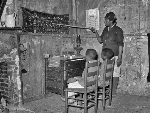"""Homeschooled:"" 1939,  Sharecropper mother teaching children numbers and alphabet at home.  Louisiana."