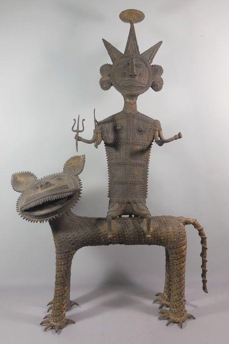 """Groot en zwaar (126 kg) sculptuur van een stamhoofd Dhokra- India - ca. 1930  Dhokra art sculptuur afkomstig uit India uit de Orissa regio. Groot en zwaar exemplaar gemaakt uit twee delen (zie foto). Tribaal figuur vermoedelijk stamhoofd op een katachtige. Vervaardigd van een koperlegering op basis van de """"verloren was"""" techniek. Dit betekend dat het object uniek is er is er maar één van in de wereld.De vaklieden uit de Orissa regio maken al duizenden jaren bijzondere metalen voorwerpen via…"""