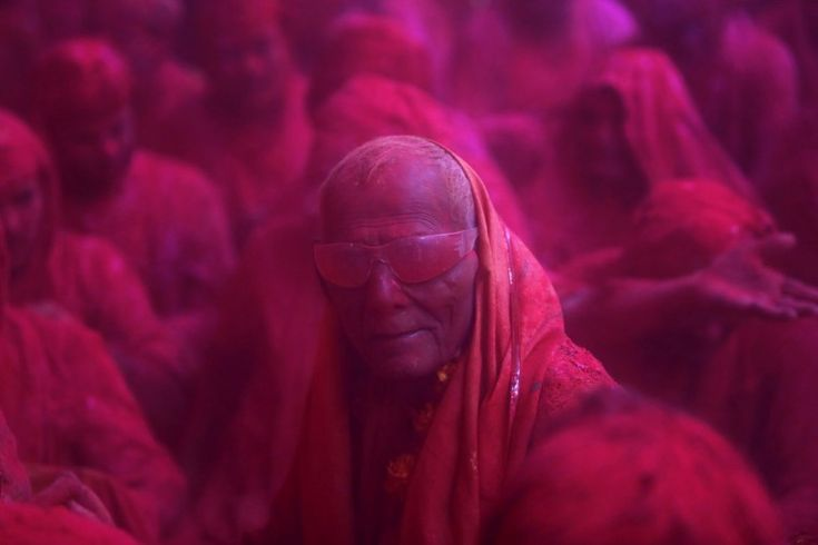 A Hindu devotee looks on in a cloud of colored powder inside a temple during Lathmar Holi at the village of Barsana