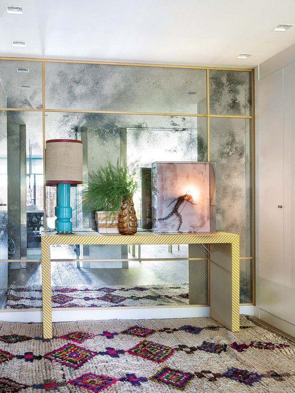 PARED FORRADA DE ESPEJO En la entrada, la pared forrada de espejo envejecido con palillería dorada proporciona una perspectiva del salón. La consola se ha actualizado con una tela de Blasco & Blasco. Sobre ella, cuadro de Lorna Smith, de Encajarte, y lámpara adquirida en Aromas de Campo.