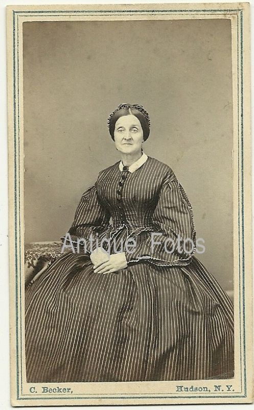 High bodice, double point at waist; box pleated full sleeve shaped at wrist; pleated skirt. Sleeves trimmed with ruched ribbon. Shown with small white collar. A.BETHKE