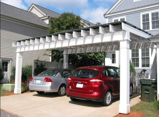 A carport in front of an actual house with solar panels.