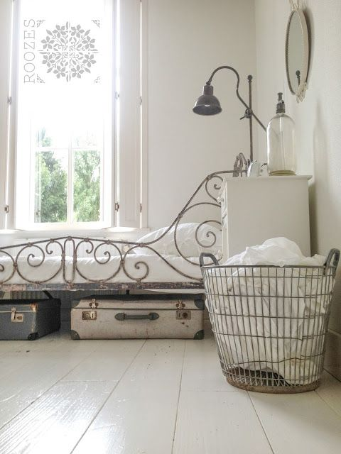 Wire laundry basket, vintage suitcase storage, metal lamp, and crisp white everywhere.  Love! #bedroomideas #vintagesuitcase