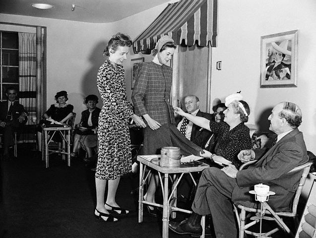 Clare McCardell in the showroom, the finished outfit is on the model.  Seated are buyers from all over the country.  After seeing the new creations modeled, they place orders for fall.   Image by Bettmann/CORBIS