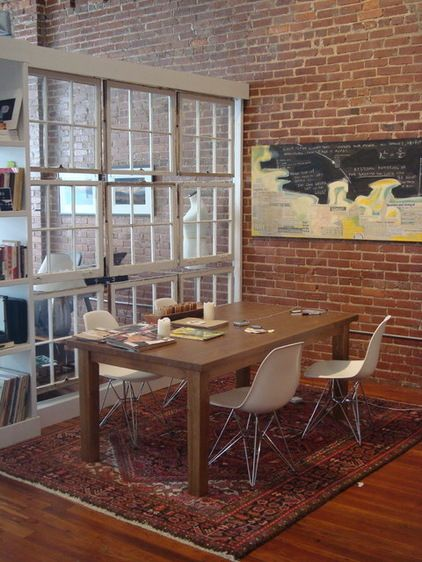 Old windows also repurpose into an inventive room or office divider. These reclaimed windows provide separation between the living and dining areas while admitting light and views. They make a big statement without taking up much square footage.