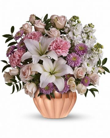 The exquisite bouquet includes light pink spray roses, white lilies, pink carnations, white stock and lavender cushion spray chrysanthemums accented with fresh greenery.