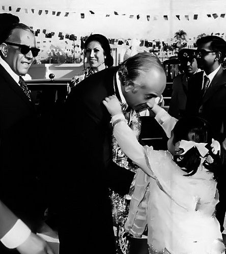 A child garlands Zulfikar Ali Bhutto as my father looks on - 1975