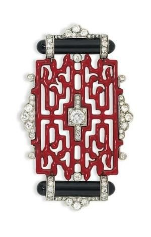 AN ART DECO ENAMEL AND DIAMOND BROOCH, BY CARTIER Of Oriental design, composed of a red enamel openwork panel, with old brilliant-cut diamond centre, mounted between polished onyx baton accents within a further diamond frame, circa 1925, 5.4cm wide Signed Cartier HSA, no.00038 by corrine