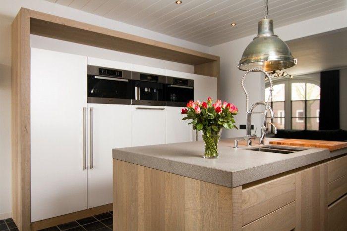 Keuken met eiken gebandzaagde fronten in combinatie met dekkend wit gespoten. Composiet blad