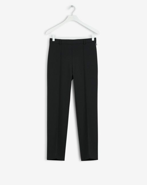 A narrow pant with a higher waist and a straight, cropped leg. Sewn press  crease at the front.
