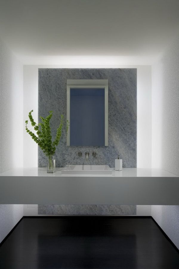 The guest bath is crisp, and inviting with an impeccable marble façade, and modern basin helping to pull together the geometric modernism of the home. -