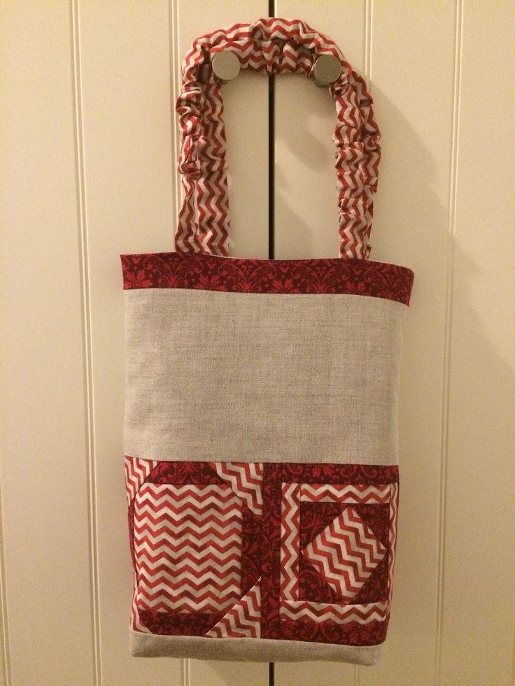 """Bolsa de lino con cuatro bloques en telas entonadas en rojo. Patrón de """"A punto de patch"""""""