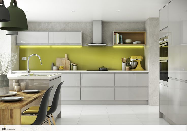 The fresh pop of green splashback keeps this grey gloss handless kitchen bang on trend. The high gloss units contrast in texture against the concrete finish of the kitchen walls. Concealed downlighters illuminate and highlight the glass splashback with more pops of lemon used in the kitchen accessories. Tonal pendant lights over the solid oak dining table created with worktops utilising the island. Textured ceramics an woods add life to the open plan kitchen.