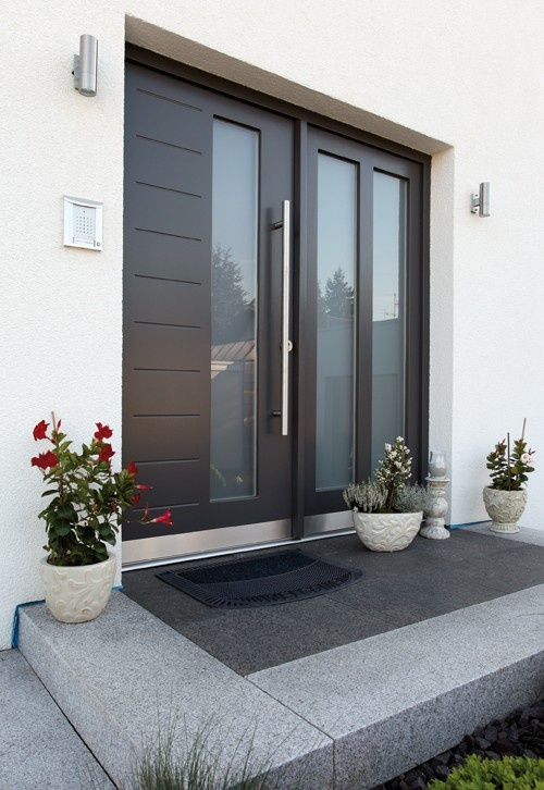 Modern front door with opaque glass sidelight window. Long vertical door pull…