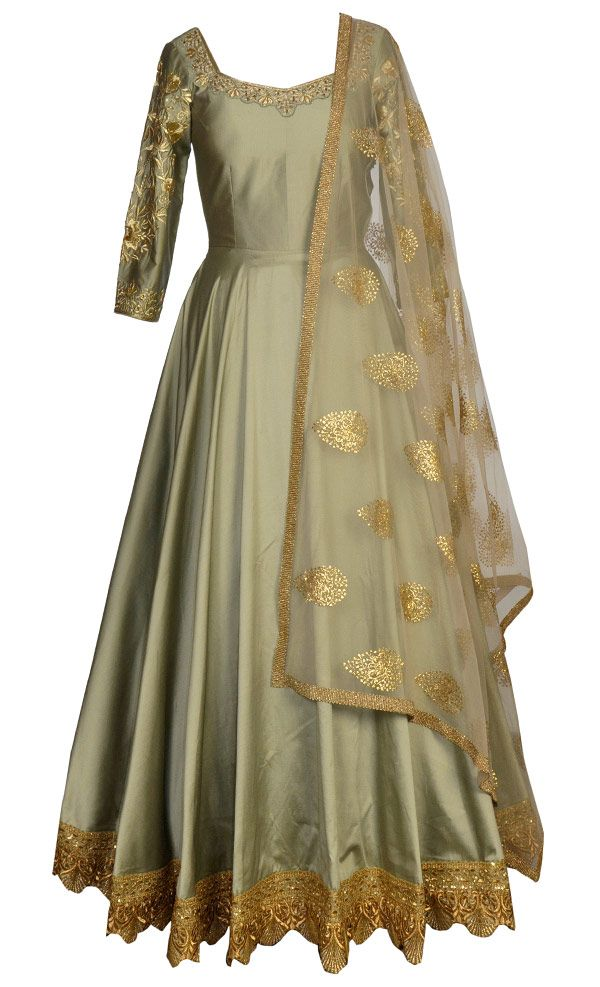 This set features a light olive green flared floor length suit in silk base with beautiful gold zari, cutdana, slight sequins and swarovski hand embroidery around the neckline and sleeves. It has a sheer back with matching dori tie up with gold tassleed hangings and gold zari and sequns embellished applique border. It is paired with a matching net dupatta with gold badla embellished all over botis and zari embellished border and comes with a matching churidar pants. This creation is designed…