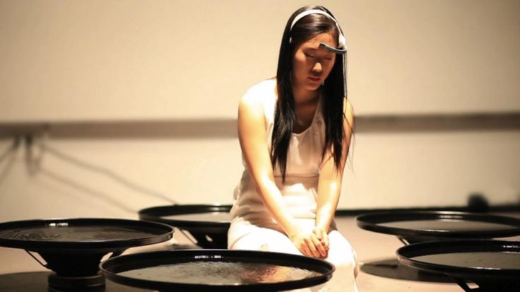 Artist Lisa Park's performative piece <i>Eunoia</i> uses an EEG sensor and her brain to interact with dishes of water.