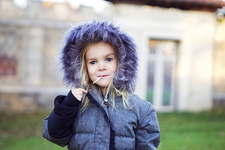 Cute toddler in warm winter jacket from Peekaboo Beans. Charcoal winter jacket with fur lined hood.
