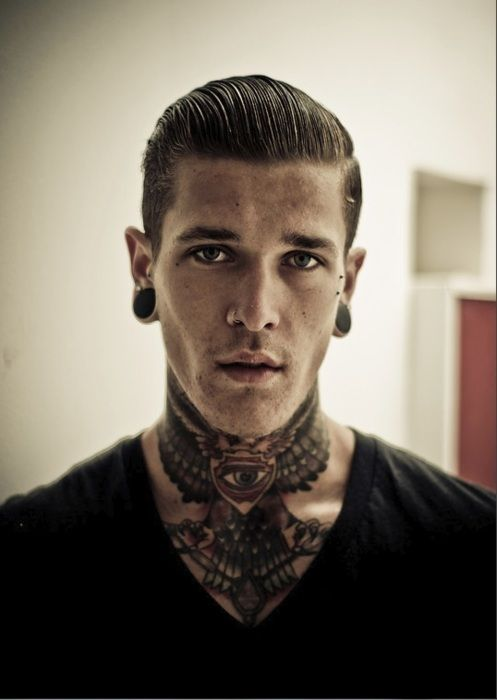 tattooed guy. neck tattoo. wings. ear stretchers.