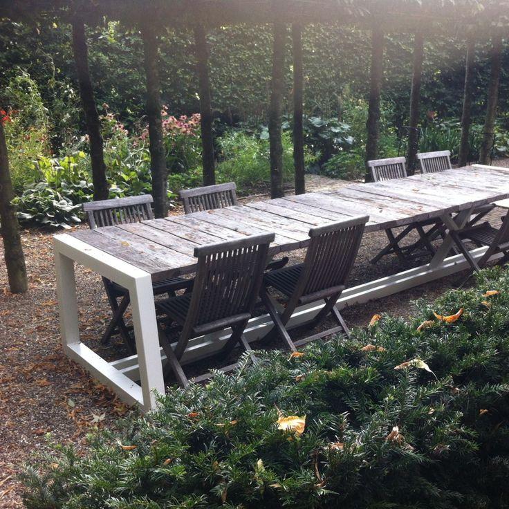 Buitentafel van ruim 4 meter lang. Het onderstel is gepoedercoat in een witte kleur en steekt mooi af bij het houtwerk. #tuintafel ontwerp: Dutchreddesign