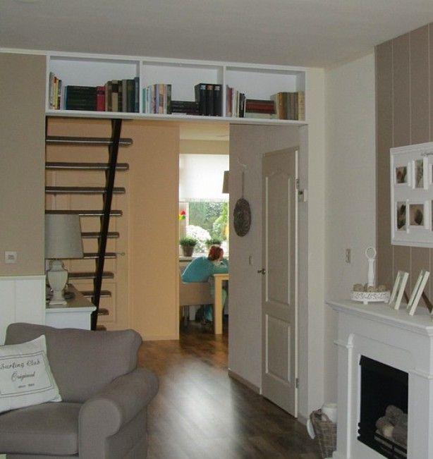 Boekenkast tussen woonkamer en keuken, gemaakt van meubelpanelen.