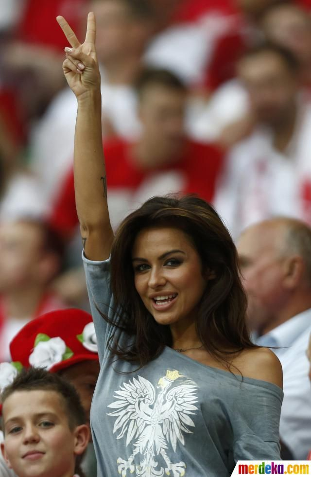 Fan cantik Polandia memberi sinyal V (victory-kemenangan) bagi Polandia sebelum laga dimulai.