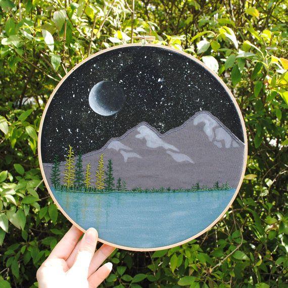 Dans cette pièce mixte, le paysage de montagne est créé en utilisant des couches de tissu, peinture acrylique et points de suture. L'éclaboussure peint étoiles donnent le ciel un look unique, complété par le croissant de lune. Les arbres ont été cousus à la main, avec des reflets subtils peints dans l'eau ci-dessous. Ce cercle à broder d'one-of-a-kind est sûr d'ajouter un peu de caractère et de charme à n'importe quel espace.  Détails : -cadre hoop broderie en bois 10(25,4 CM/10 pouces) ...