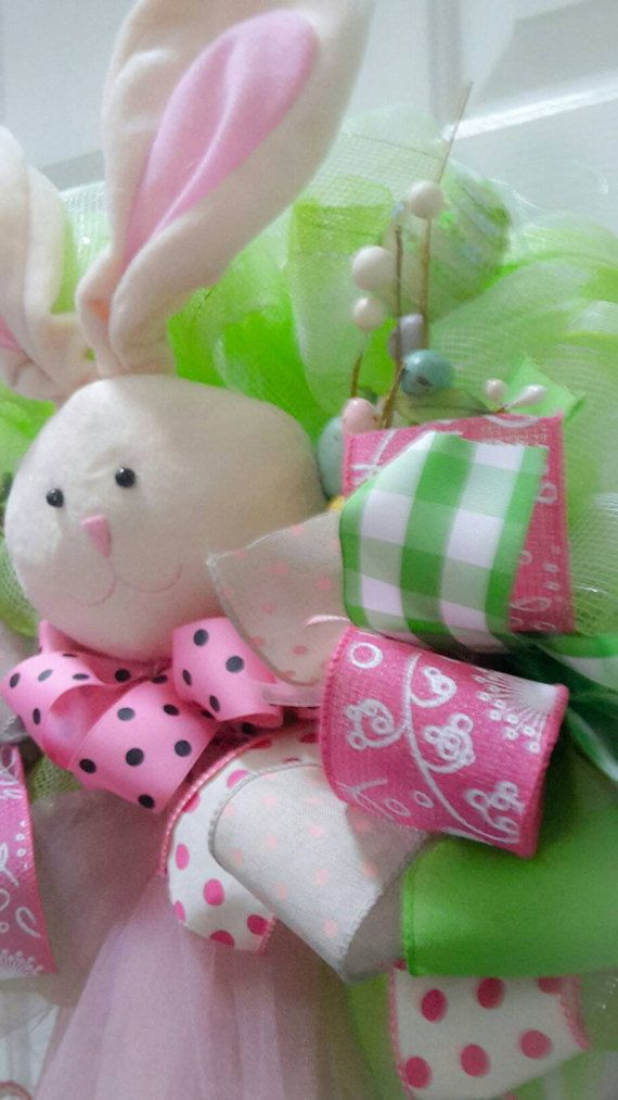 Green and white verigated mesh on a Styrofoam wreath form. A plush bunny with floppy ears wearing a pink and black polka-dot ribbon bow tie and a mauve tule skirt. Surrounded with spring funky bows, a few Easter eggs and Easter picks. This bunny has two plush bunny feet wearing