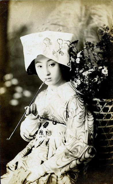 Dressed for an Odori 1920s  A Geiko (Geisha) in costume for an Odori (Dance) as a country girl, smoking a pipe and carrying a basket of flowers on her back.