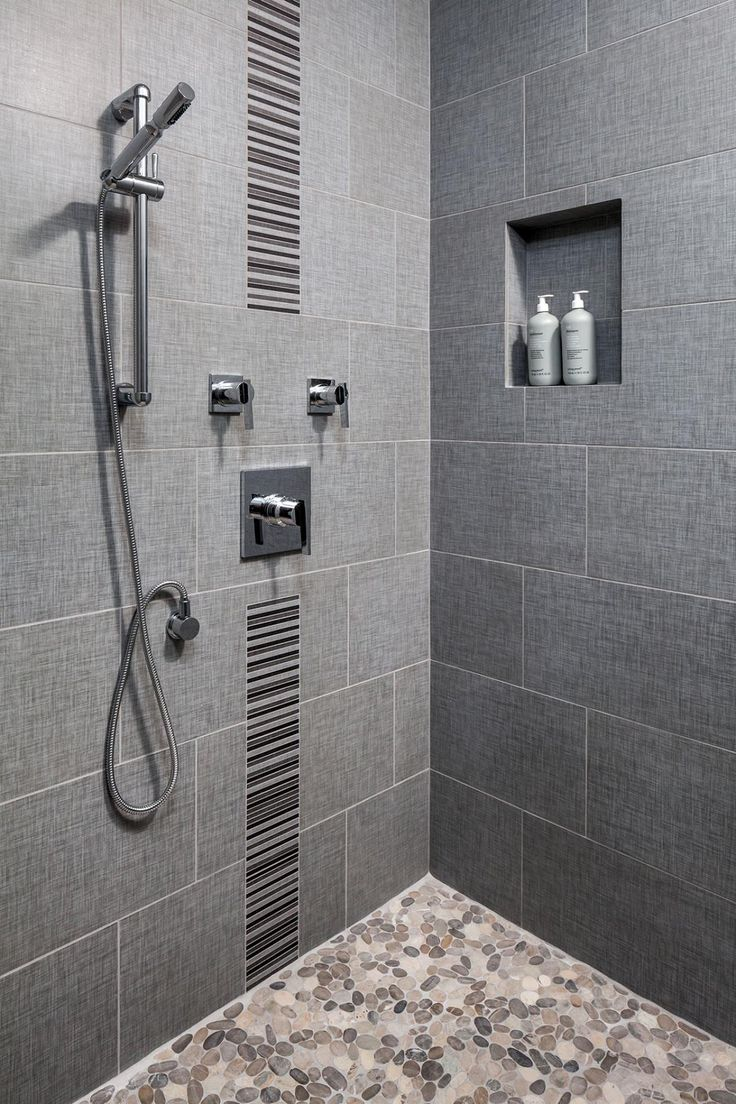 This walk-in shower is decked out with chrome Danze fixtures, an accent stripe, pebble tile flooring and a niche for shower essentials.