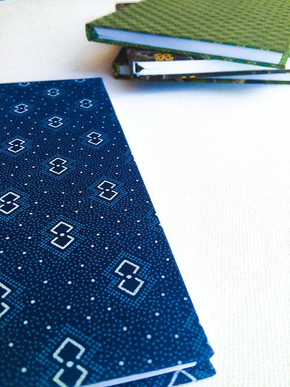 A handmade A5 notebook covered in authentic Shweshwe material from South Africa. This print features a white and blue overlapping diamond motif. #African #notebook #fabric $12