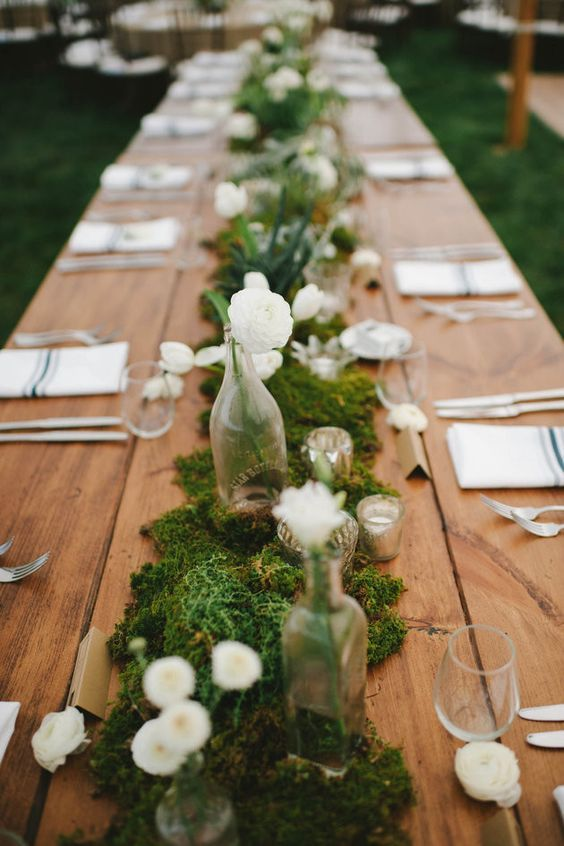 moss table runner decorated with white flowers, bottle vases and candles                                                                                                                                                                                 More
