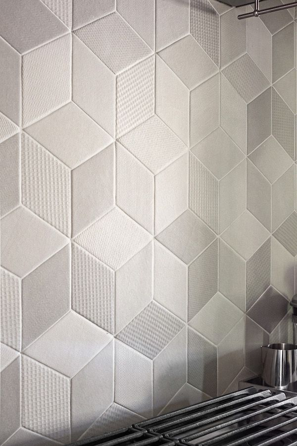 A gray-toned kitchen remodel features a textured, hexagonal-patterned tile backsplash from Mutina Tex.