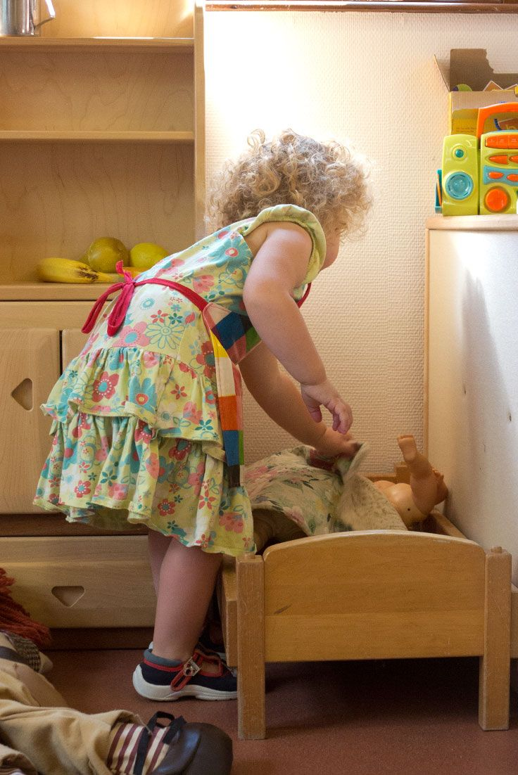 Putting a doll to bed is a comforting, calming moment for busy children.