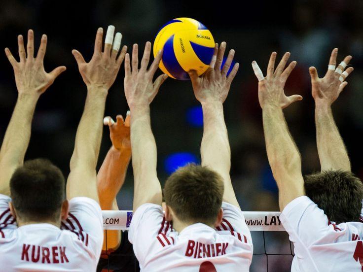 From left, Poland's Bartosz Kurek, Mateusz Bieniek and Michal Kubiak block a shot by the German team during the Olympics qualifying third-place men's volleyball match in Berlin.  Gregor Fischer, EPA
