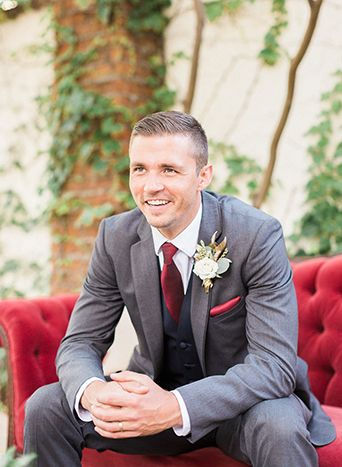 Use a grey suit with pops of burgundy, to create this unique grooms look!