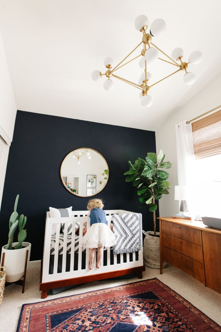 a sister and brother moment // boy nursery with dark navy accent wall, ornate rug, fiddled fig tree, bubble chandelier and mid-century credenza