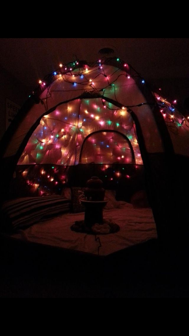 Tent in the living room covered in lights with blankets and snacks. Such a cute date in idea
